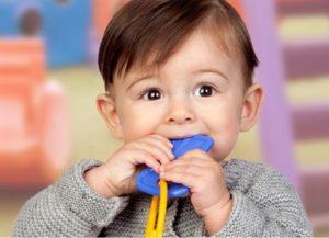 Ребенок с игрушкой во рту