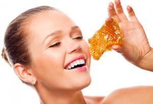 Девушка кушает мед