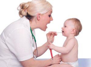 Врач обследует полость рта у ребенка
