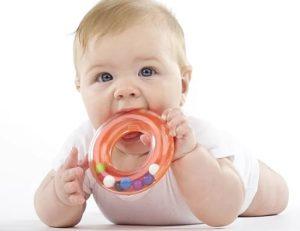Ребенок с погремушкой во рту