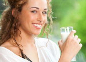 Девушка держит стакан с кефиром